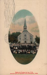 Old colored photograph of an oval shape, long shot of a crowd posing for a photo in front of a small white and blue church.