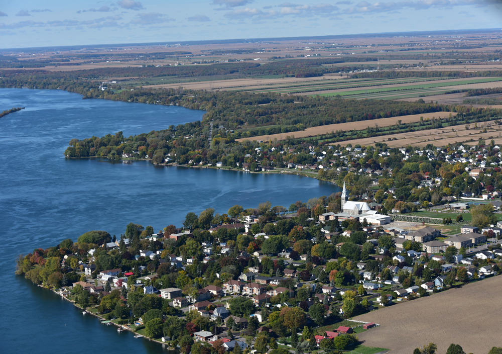 Color photograph, aerial view of an urban area on the waterfront of a large river, in the center, a church and its steeple, in the background, extensive farm lands.