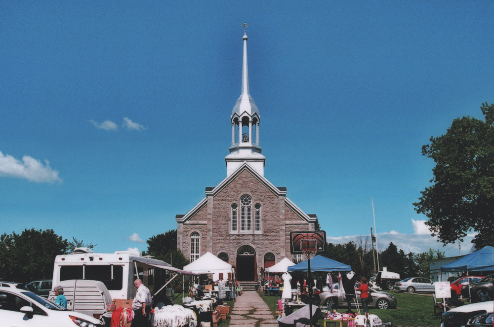 Color photograph, facade of a large stone church in front of which stand people, cars, tables and canopies.