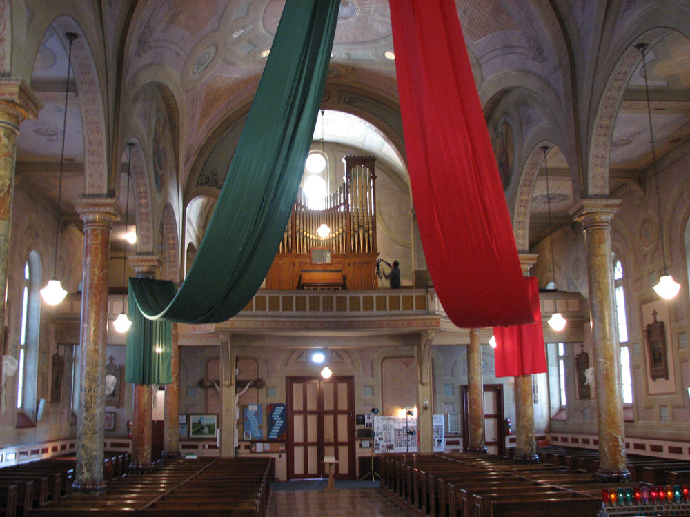 Color photograph, long shot of church interior richly decorated with murals on the walls and columns, two large pieces of fabric green and red are suspended above the nave. On the back gallery, a photograph and a large pipe organ.