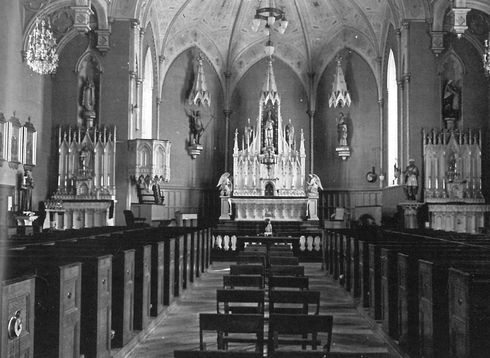 Old black and white photograph, long shot of church interior, in the background, liturgical furnishings and many statues, in the foreground, multiple rows of wooden pews.
