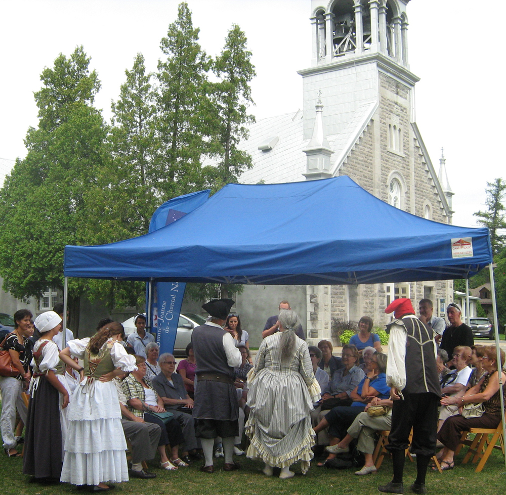 Color photograph, close-up of actors participating in a cultural activity under a canopy between a chapel and a stone church.