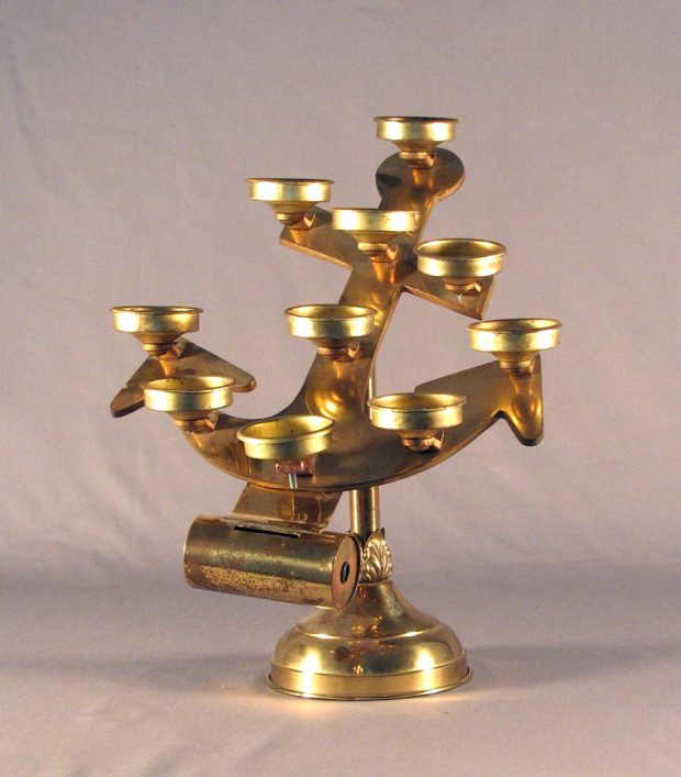 Color photograph, close-up of an anchor-shaped brass religious object with many cells in which can be placed votive candles.