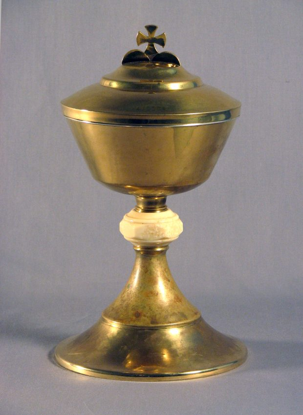Color photograph, close-up of a religious object made of brass, gold and ivory, in the shape of a stemmed glass and cross-topped lid.