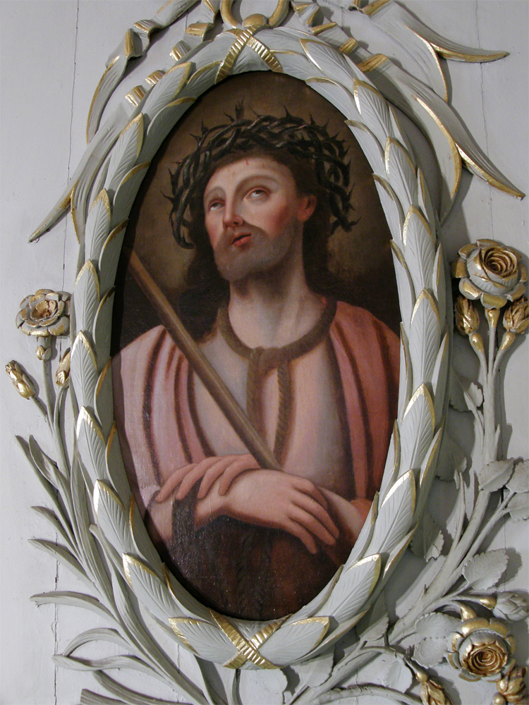 Color photograph, close-up of a painting of a man looking to the heavens and wearing a crown of thorns on his head. The painting is in an oval frame sculpted out of wood and covered in gold leaf.