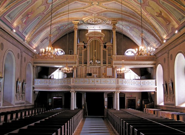 Color photograph, long shot of church interior with decorated dome, in the background a platform and large copper pipe organ, in the foreground, rows of wood pews.