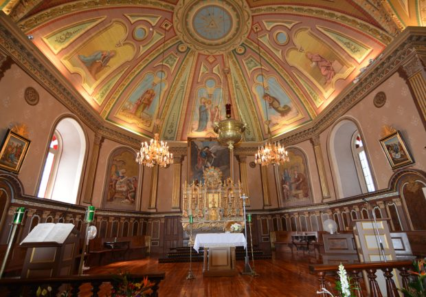 : Color photograph, long shot, church interior richly decorated and lit with a large vaulted ceiling, decorated with religious characters, liturgical furnishings accented with gold and walls in a semicircle shape are covered with woodwork and gold accents.