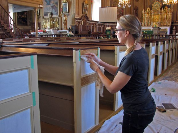 Color photograph, close-up of a woman kneeling on the side of a pew. She is gloved and working with a rag to restore a wood pew in a richly decorated church.