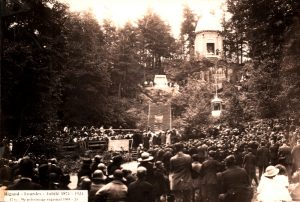 Old black and white photograph, a crowd is assembled at the foot of a large hill, a large staircase leads to a rotunda that is surrounded by trees.
