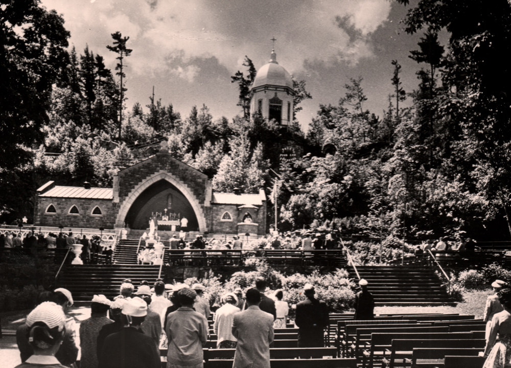 Old black and white photograph, long shot, in the foreground, pilgrims stand at their benches during an outdoor religious ceremony, in the background, an outdoor chapel in the middle of a hill topped with a rotunda and surrounded by trees.