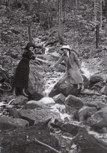 Old black and white photograph, close-up of two women each holding a cup and bending to draw water from a small stream flowing between large boulders.