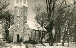Old black and white photograph, long shot taken in winter, façade and side-view of a stone church and its square steeple.