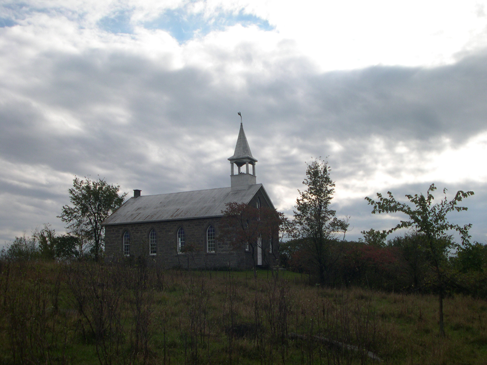 Color photograph, long show of side-view of a small country stone church surrounded by trees and a cloudy sky.