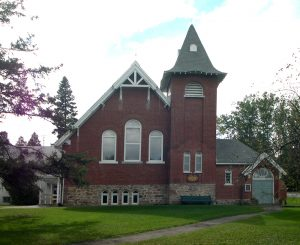 Color photograph, long shot of a red brick church facade with a steep sloped roof and square steeple, in the front, a sidewalk leads to a wood door on the righthand side of the building.