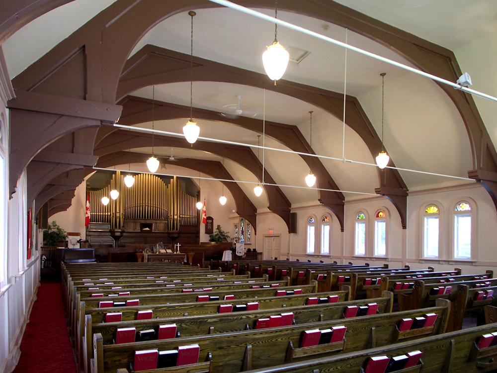 Color photograph, long shot of a church interior with exposed wood beams, in the foreground, wood pews holding red books, in the background, a large copper pipe organ.