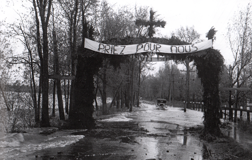 Old black and white photograph, long shot of a car driving on a flooded road bordered by trees above which a cross-topped banner reads: Pray for us.