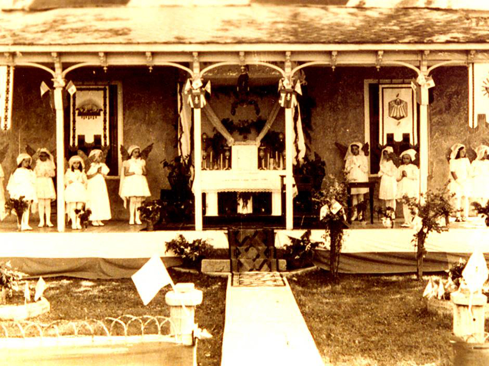 Old sepia photograph, young girls, hands joined, all dressed in white stand on a house porch decorated with flags and religious accessories, the girls personify angels as they stand on each side of an altar of repose.
