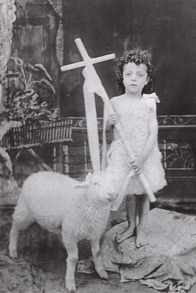Old black and white photograph, close-up of a young boy holding a cross and wearing sheepskin, standing next to a small sheep.