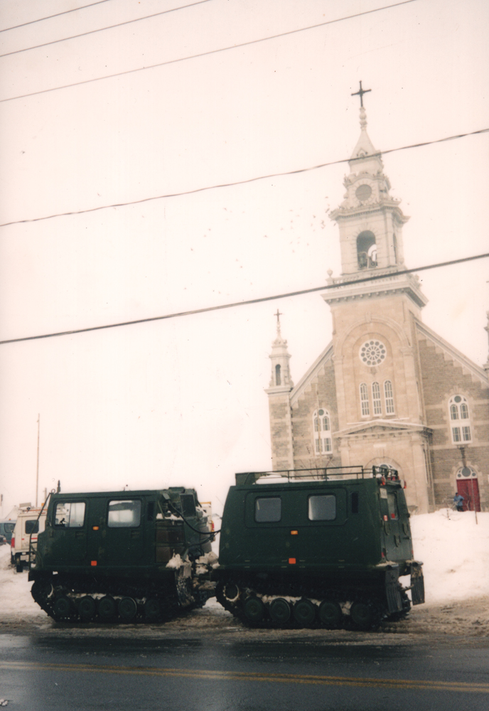 Color photograph taken in winter, long shot, two military vehicles are parked near the front door of a large stone church.