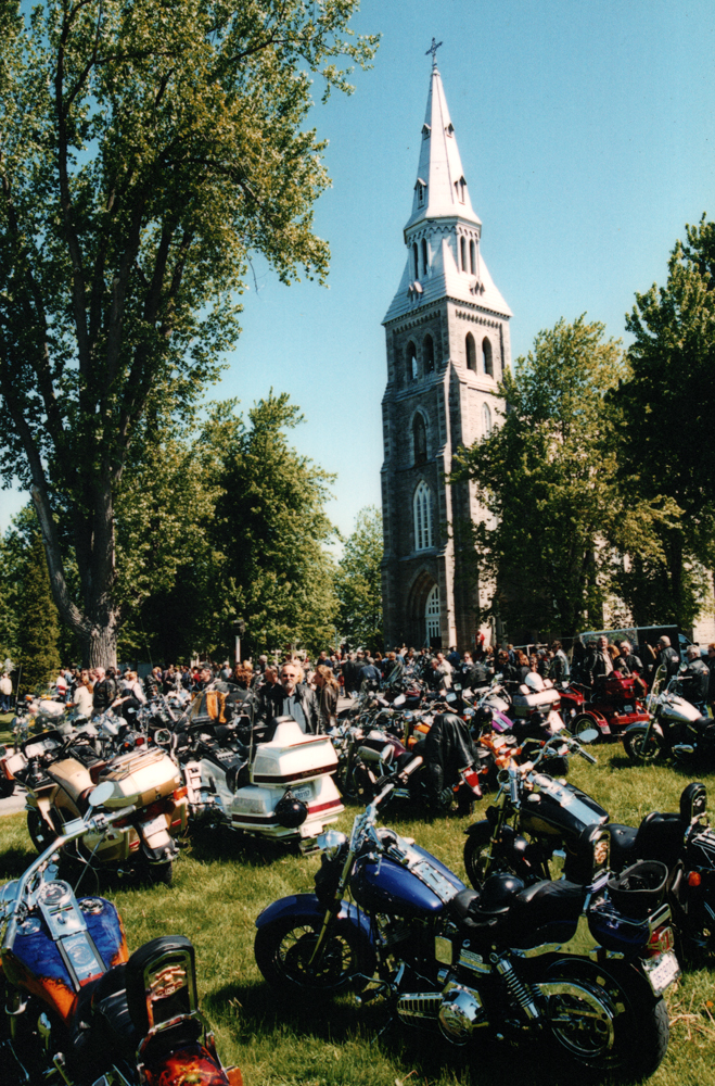 Color photograph, long shot of motorcycles and a crowd on a large lot surrounded by trees in front of a church.