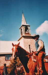 Color photograph, close-up of a cowboy on his horse next to a stone church and its steeple.