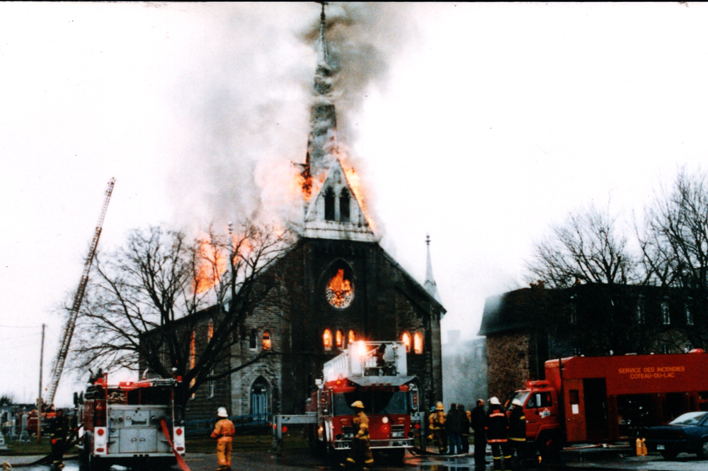 Color photograph, long shot of firefighters with a crane and many trucks, attempting to extinguish a church on fire whose steeple, roof and windows are in flames.