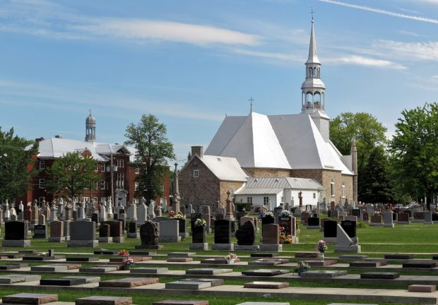 Color photograph, long show, in the foreground, a large cemetery, in the background, a stone church and its steeple. To the left of the building, a large red brick structure topped with a dome.