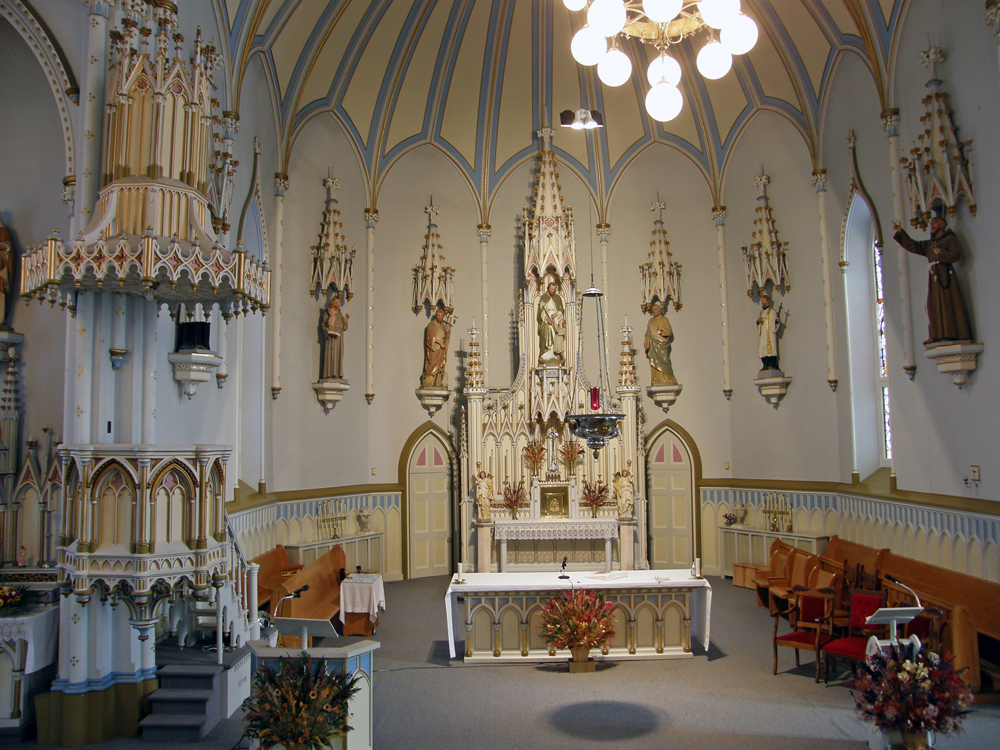 Interior view of a semicircle section of a church, long shot of walls with many religious plaster statues placed on wooden pedestals, above them are sculpted wooden canopies, in the center, liturgical furnishings.