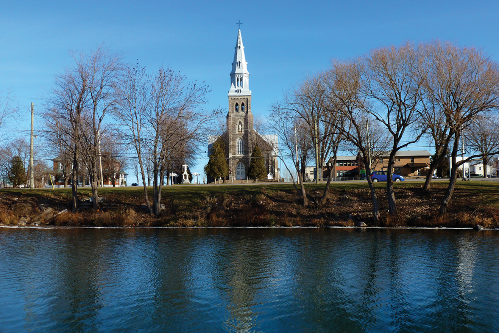 Color photograph, long shot, in the foreground, a river, riverside and trees, in the background, the façade of a large stone church and steeple.