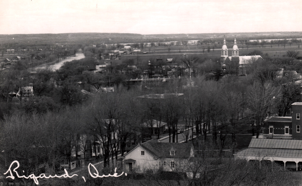 Old black and white photograph, wide aerial view of steeples breaking through trees and houses, in the background, a river.