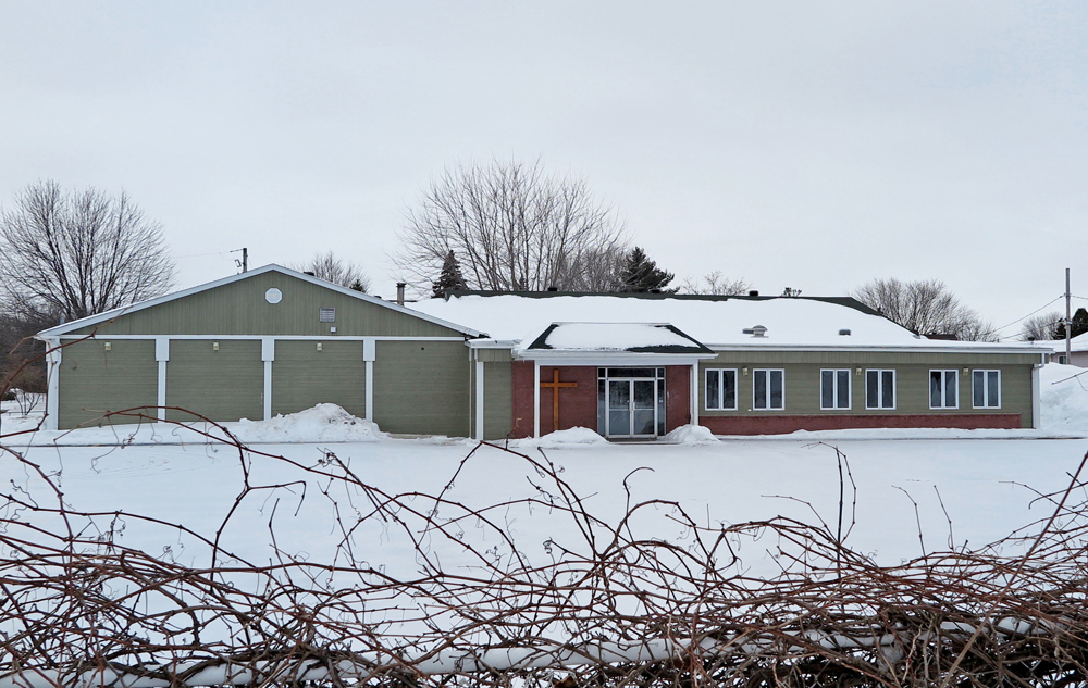 Color photograph taken in winter, long shot of facade of large rectangular building with flat roof and beige vinyl siding with a few windows, next to the front door, a large brown cross, in the foreground, a fence filled with vines.