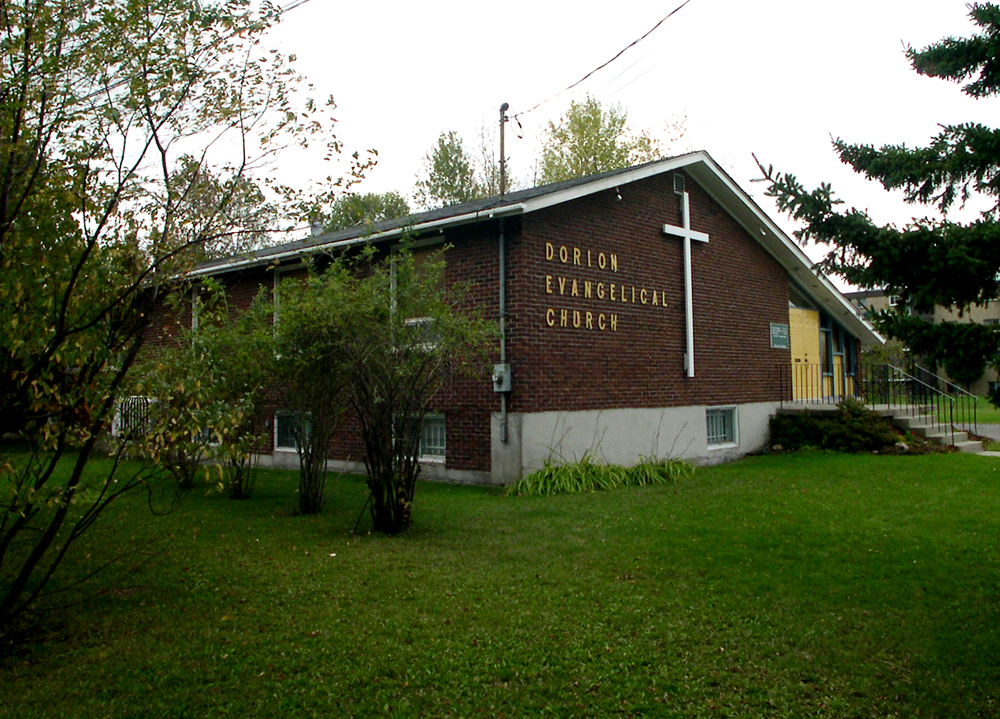 Color photograph, long shot of side-view of a brown brick building with a sloped roof, on the façade, a large white cross next to which is written: Dorion Evangelical Church.