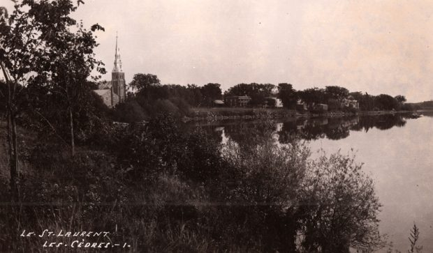 Old black and white photograph, large body of water, trees and vegetation in the foreground, a church steeple and a row of small houses in the background.