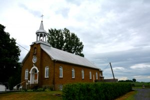 Color photograph, red brick church with steeple and statue in an alcove, on the church porch is garden furniture, on the right of the building, a boarded up window and a concrete slab annex, fields in the background.