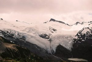 A massive glacier covers the slope and obscures the peaks above. The creep of the glacier extends to the hanging alpine valley floor. Grey clouds swirl above the high peaks.