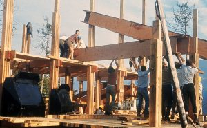 Several members work at construction, raising a large wooden floor joist and maneuvering it into position.