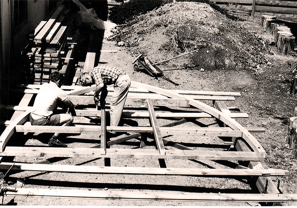The arch frame sits off the ground supported by two other pieces of wood. Two men are hunched over working on pieces of the arch on the left hand side. Other lumber sits stacked neatly behind next to a house.