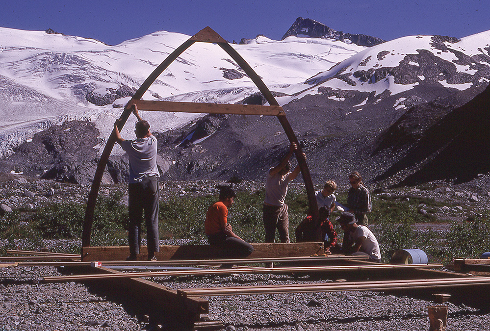 The foundations have been built and several pieces of the floor stretch across the width above the rocky ground below. Two men hold up the first wooden arch, another sits in the middle of the arch while another group work to attach the arch to the foundation.