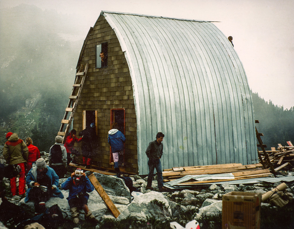 The Hut structure is completed with aluminum siding. A man looks out the top floor window above the main entryway. Other members are seen working on the front end wall and in front of the entrance to the Hut.