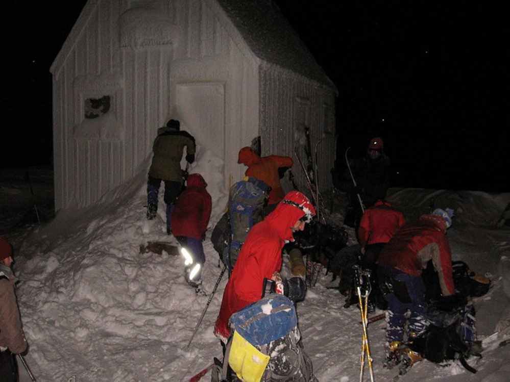 Three members near the front door of the hut are busy clearing the snow away. Off to their right a group of members are taking off ski equipment and organizing gear.