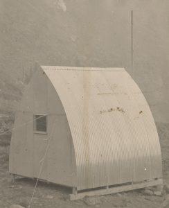 Vue arrière du parement métallique ondulé, refuge à voûte de style gothique comprenant une petite fenêtre carrée installée à l'emplacement prévu. En arrière-plan, un gros poteau et un escarpement rocailleux.