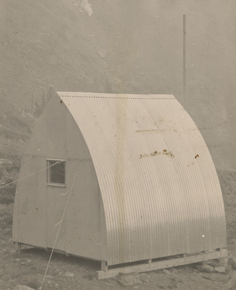 Rear view of the corrugated metal siding, gothic arch hut with small square window installed at its final location. A large pole and steep rocky slope are in the background.