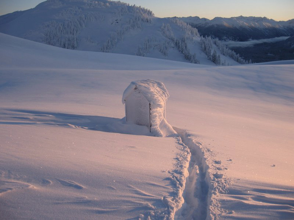 Lone outhouse in deep snow with a path cleared to its entrance