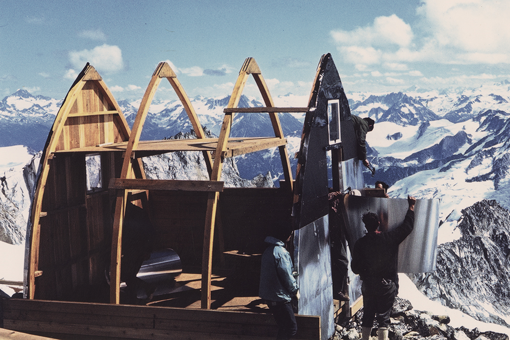 Construction on the Plummer Hut is underway. Men attach aluminum siding to one wall. A vast landscape of snowy mountains fills the background.
