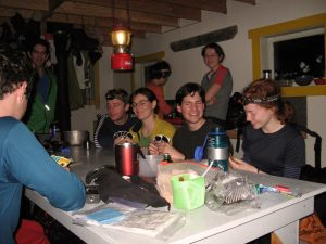 UBC-VOC Club trips have long held the tradition of playing card games. Club members are playing a game of UNO around the gray dining table inside the Hut. In the foreground, the right arm of a man wearing a blue shirt, holding his cards. A man in a green jacket stands at the far end of the table and a woman wearing a grey and red short sleeve shirt stands behind the 4 members sitting at the table. Another women in pink with her back turned is working away at the cooking station.