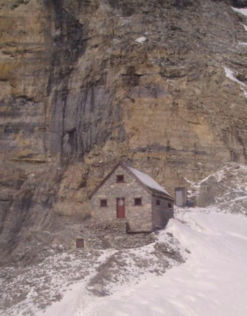 A stone shelter with an a-frame roof and a dark brown front door sits below a steep sedimentary rock face of the Rocky Mountains. In the background, the outhouse entrance is carved into the steep rock face and to the right of the Hut is a snow covered slope that runs to the edge of the image.
