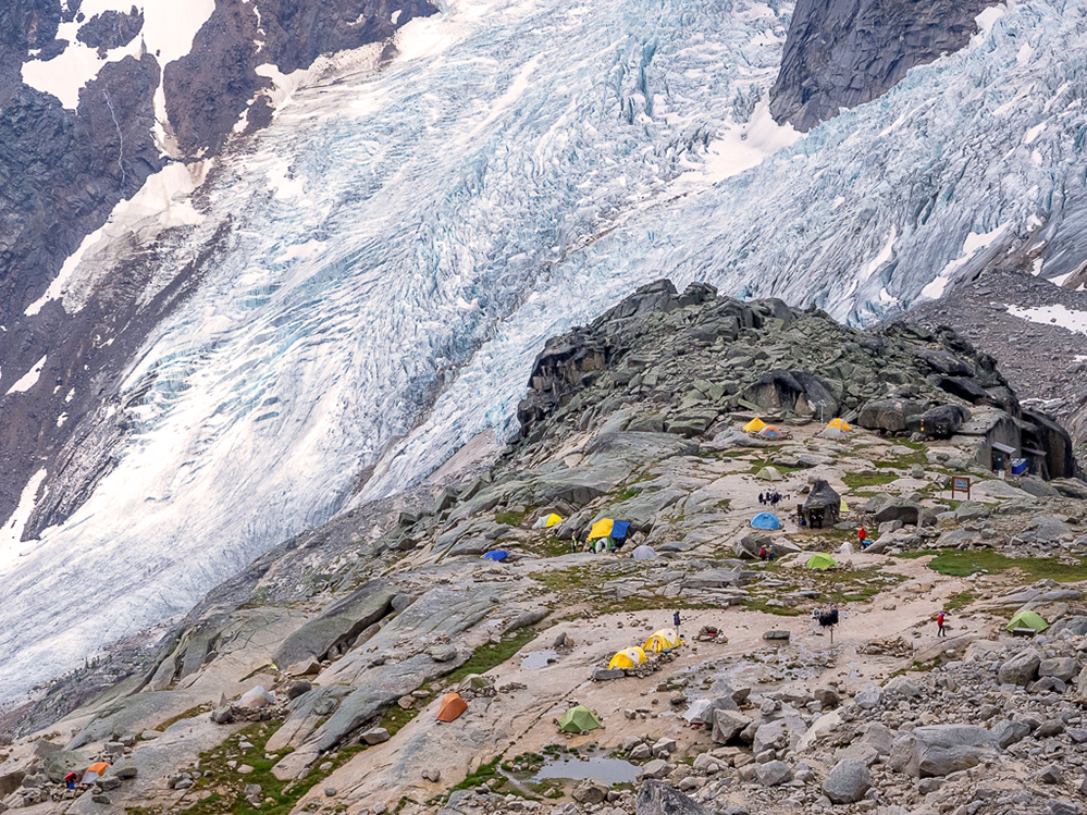 Photo looks down on a large open rock area dotted with tents located near a large glacier hanging on to a steep slope in the background.