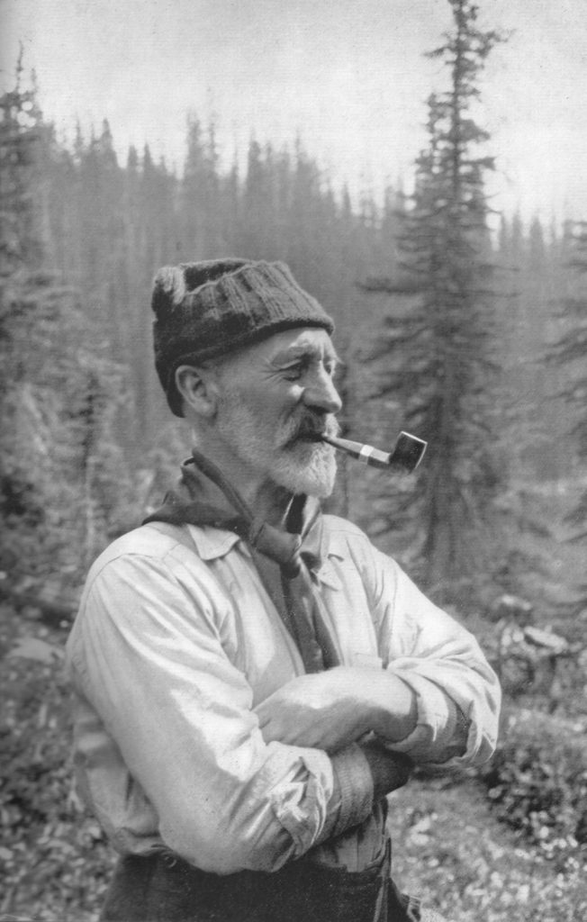 A black and white photograph of a bearded Arthur Wheeler with arms folded across his chest and pipe hanging out of his mouth, wearing a toque, scarf and a long-sleeve shirt with evergreen trees in the background.
