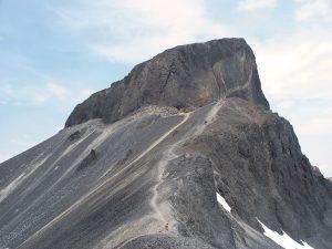 Gros plan du sombre rocher volcanique qui permet de reconnaître très facilement la crête de l'Aiguille. Une personne en chemise orange se tient près d'une crête sous l'aiguille.