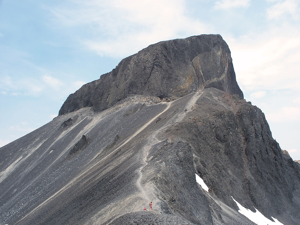 A close up of the Black volcanic rock face that makes the Tusk peak so easily identifiable. A person in an orange shirt stands along a ridge below the peak.